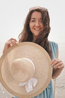 Молодая женщина в летней шляпе позирует на мосту, счастливых каникул