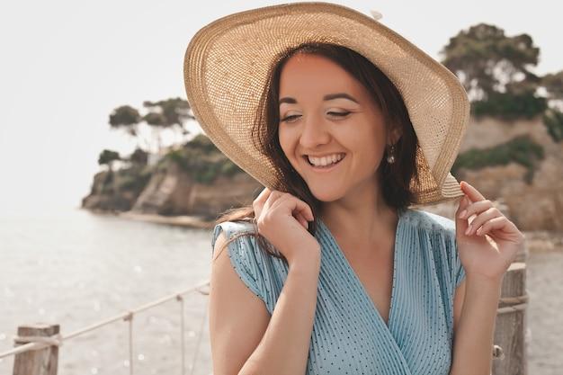 橋の上でポーズをとって夏の帽子を持つ若い女性
