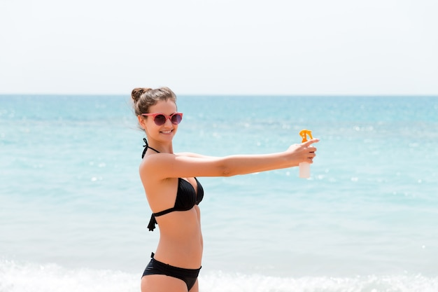 Young woman with sun protection spray for body at the beach.
