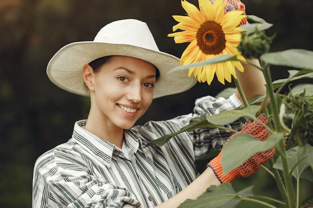 Young woman with sunflowers. lady in a hat. girl in a garden.