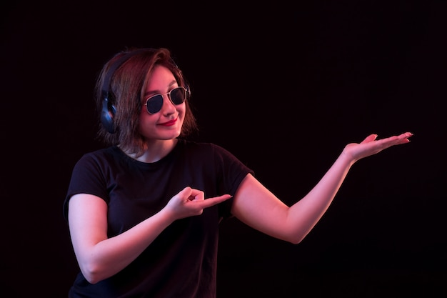 Giovane donna con gli occhiali da sole e la maglietta nera che tiene qualcosa