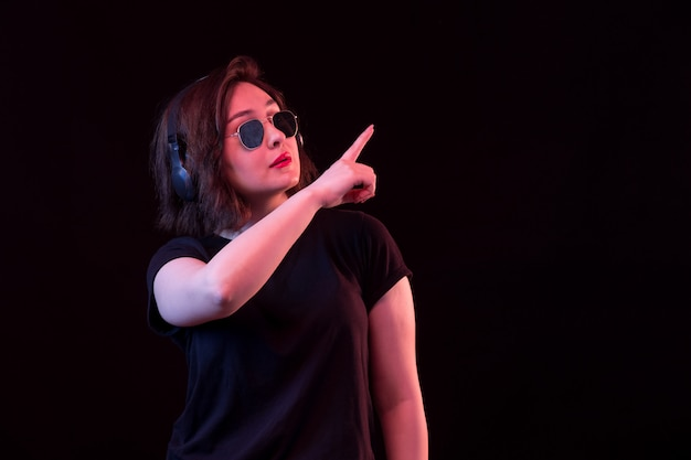 Giovane donna con occhiali da sole e t-shirt nera che punta