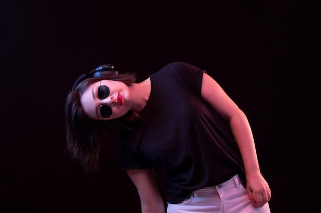 Giovane donna con occhiali da sole e maglietta nera utilizzando le cuffie
