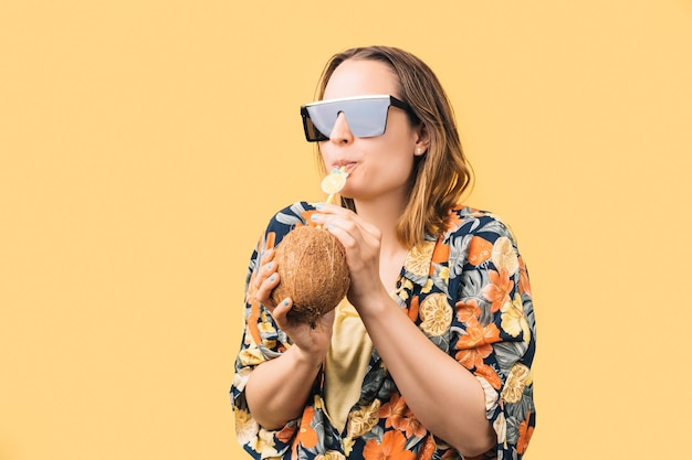Young woman with sunglasses and flowered shirt drinking coconut with plastic straw on yellow background