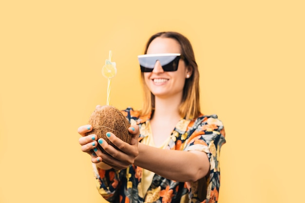 Young woman with sunglasses and flowered shirt holding coconut with plastic straw on yellow background