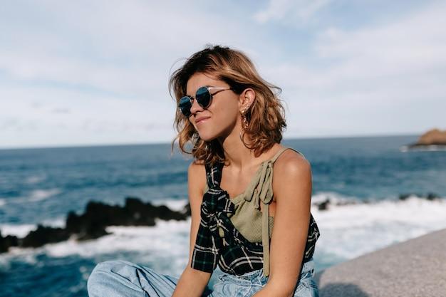 Giovane donna con occhiali da sole in posa sulla spiaggia
