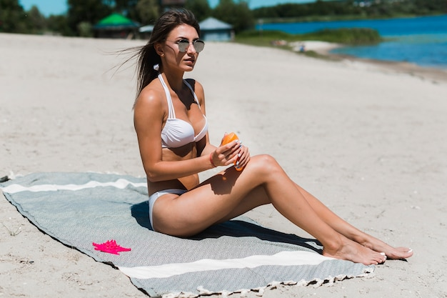 Young woman with suntan lotion on beach
