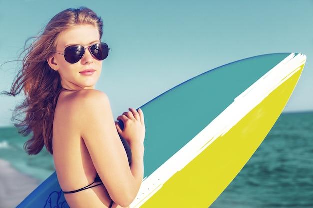ビーチでサーフボードを持つ若い女性