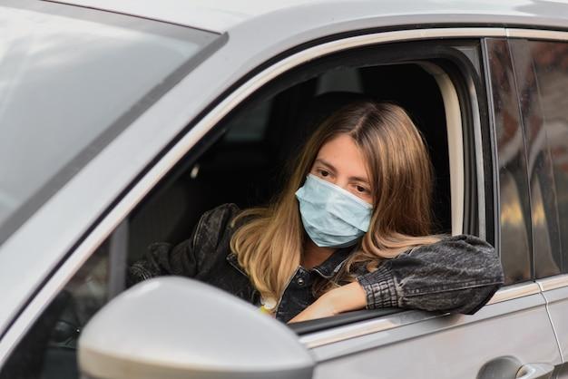 彼女の顔に手術用保護マスクを付けた若い女性が車を運転しています。安全を確保する