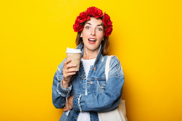 Young woman with a surprised face in a denim jacket and a wreath of red flowers on her head holding a paper cup with coffee on a yellow wall.