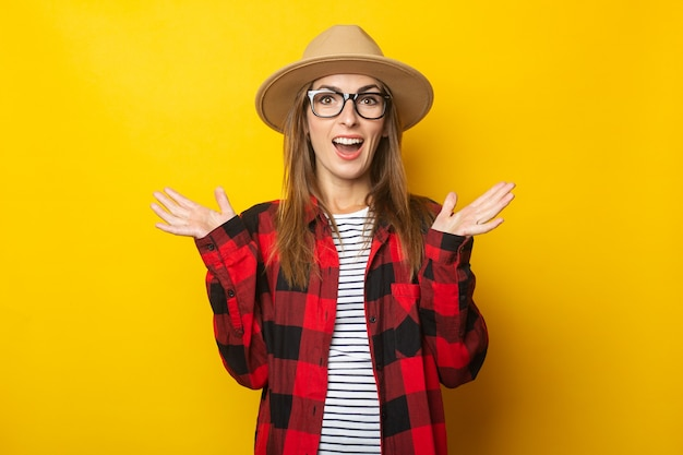 Young woman with surprised face in hat and plaid shirt on yellow.