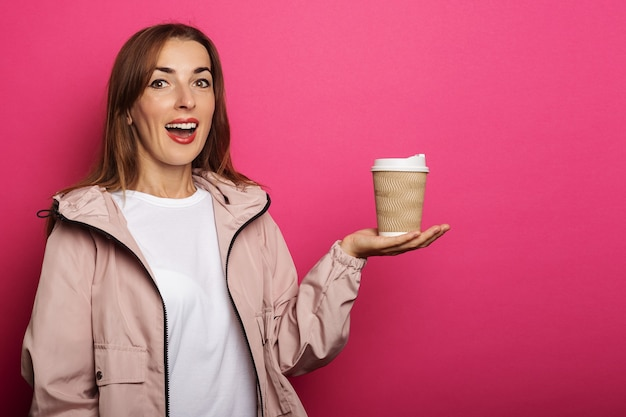 Молодая женщина с удивленным лицом держит бумажный стаканчик с кофе