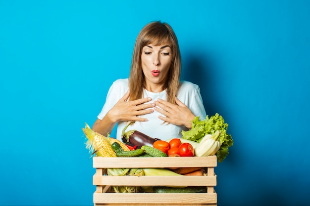 Young woman with a surprised face holds a box with fresh vegetables on blue. good harvest concept, natural product
