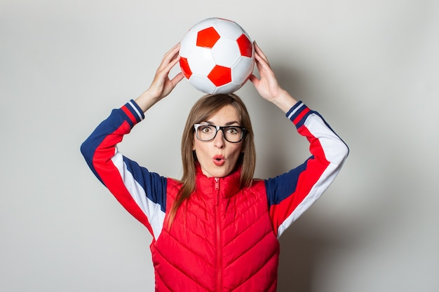 Young woman with a surprised face in a red vest holds a soccer ball above her head
