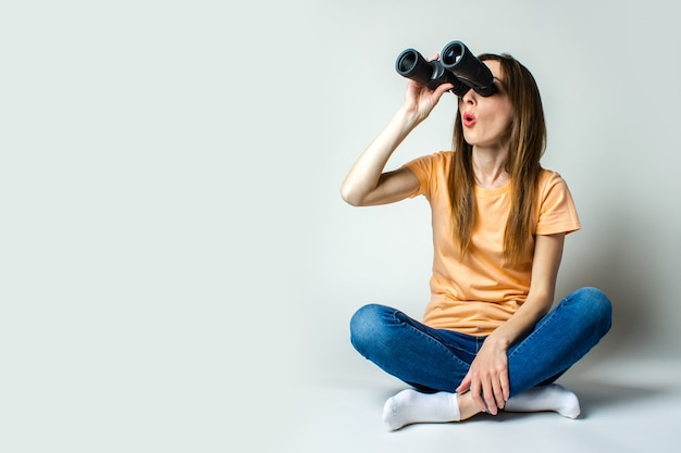 Young woman with a surprised face sitting on the floor looking through binoculars on a light background