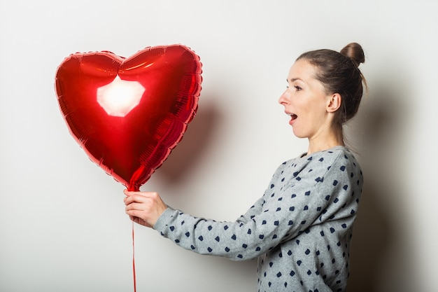 Young woman with a surprised face in a sweater and a heart air balloon on a light background. valentines day concept.