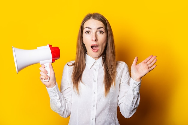 Young woman with a surprised face in a white shirt holds a megaphone in her hands on a yellow background