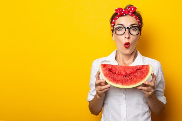 Молодая женщина с удивленным лицом с красной повязкой на голову и в очках, держа кусок арбуза на желтой стене.