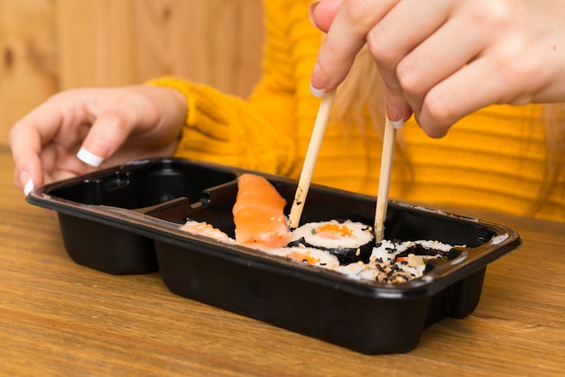 Young woman with sushi over wood background