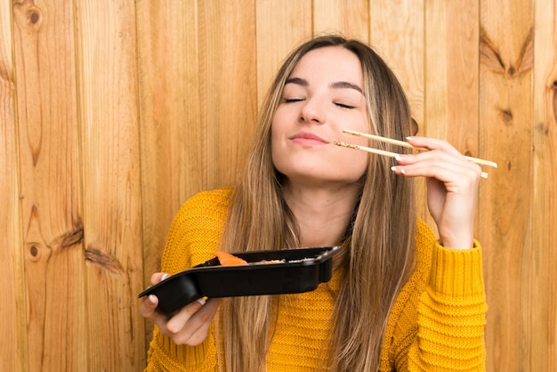 Young woman with sushi over wood wall