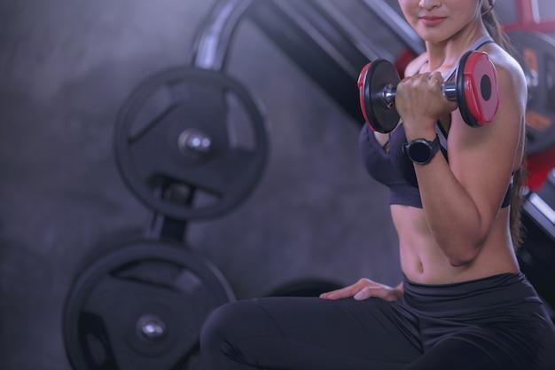 フィットネスジムでダンベルを使って運動する汗をかいた若い女性強くて健康的なコンセプト