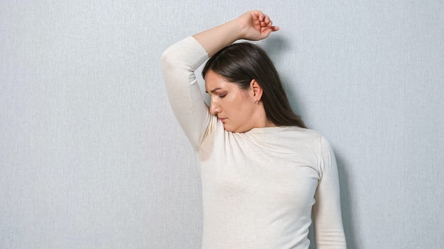 Young woman with a sweat problem under armpits. the concept smells bad. hyperhidrosis.