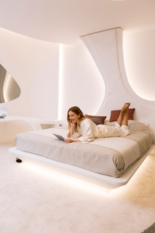 Young woman with tablet in the bed at the luxurious apartment