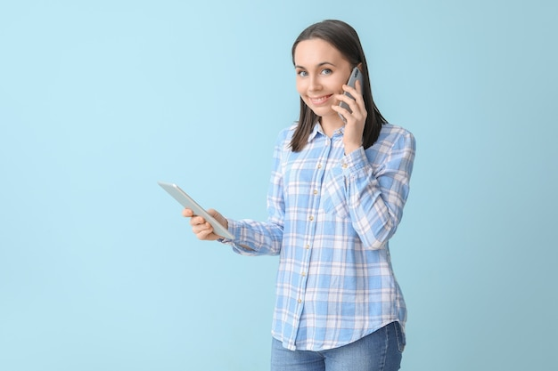 青の携帯電話で話しているタブレット コンピューターを持つ若い女性