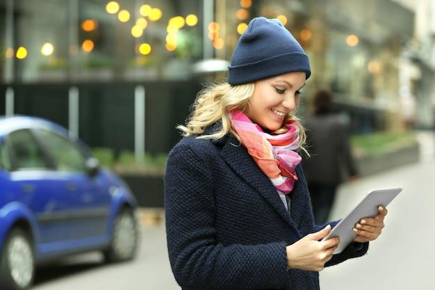 도시 거리에 태블릿을 가진 젊은 여자