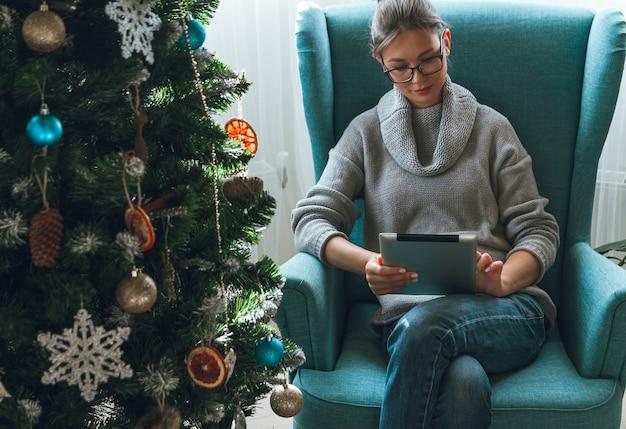 Молодая женщина с планшетом на дизайн елки