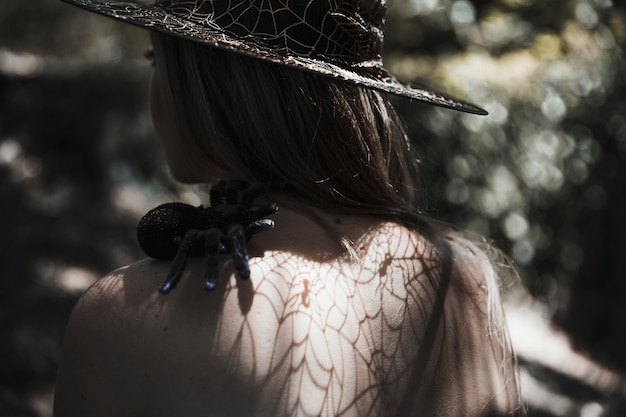 Young woman with tarantula on shoulder in forest