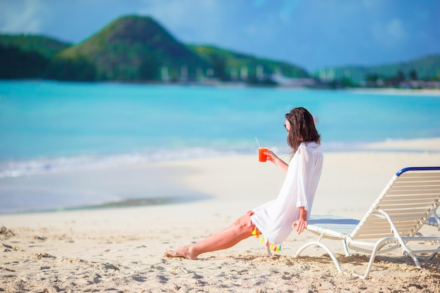 Young woman with tasty cocktail on summer vacation