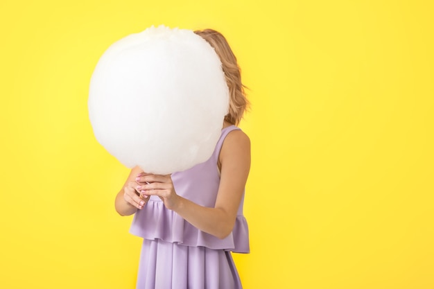 色においしい綿菓子を持つ若い女性