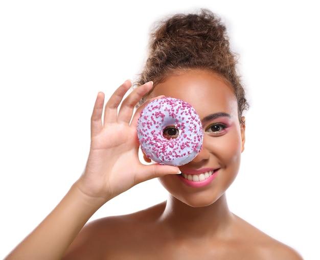 おいしいドーナツを持つ若い女性