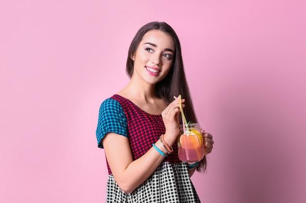 色においしいさわやかなレモネードを持つ若い女性