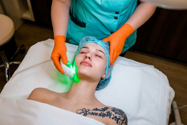 Young woman with tattoo receiving epilation laser treatment on face at beauty center..