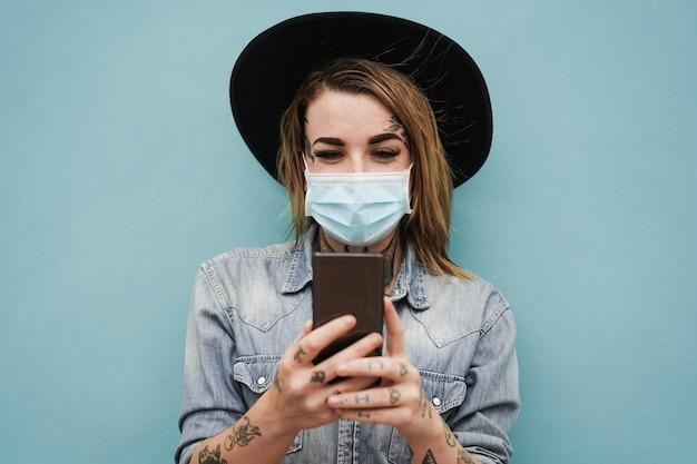 安全マスクを身に着けている屋外で携帯電話を使用して入れ墨を持つ若い女性