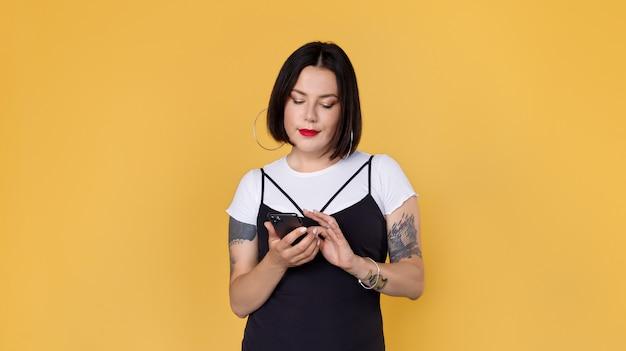Молодая женщина с татуировками с помощью смартфона