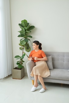 Young woman with tea cup day dreaming on couch at home