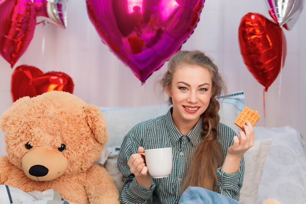 風船の中でバレンタインデーにワッフルとお茶やコーヒーと一緒に朝食をとっているテディベアの若い女性