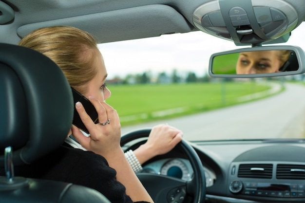 Young woman with telephone in car