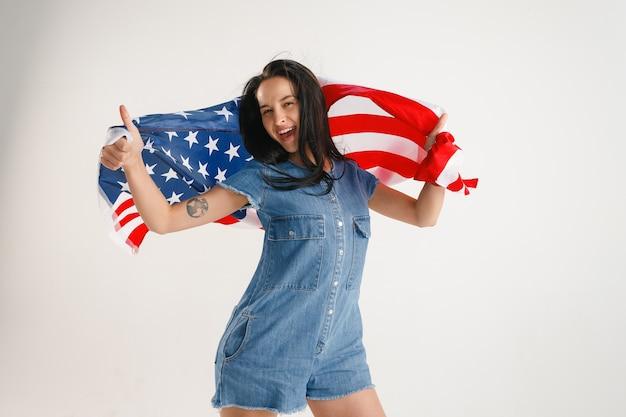 白いスタジオで隔離のアメリカ合衆国の旗を持つ若い女性。