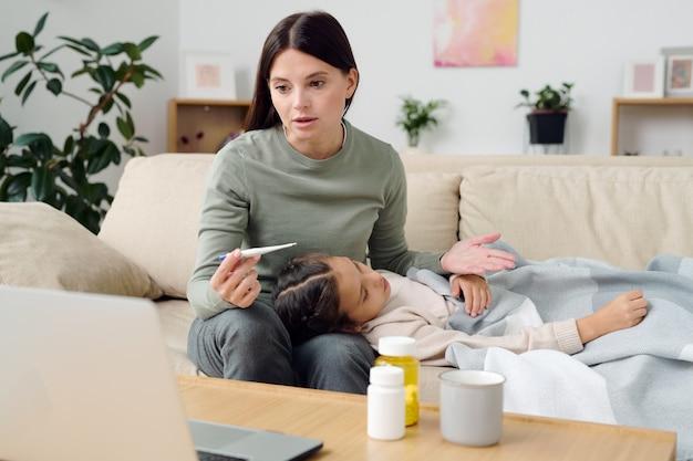 그녀 옆 소파에 앉아있는 동안 온라인 의사에게 아픈 어린 딸의 증상을 설명하는 온도계를 가진 젊은 여성