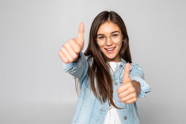 Молодая женщина с большими пальцами руки вверх изолированные над белой стеной