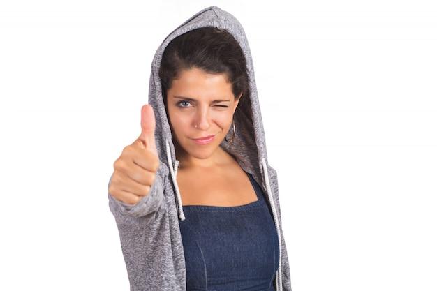 親指を持つ若い女性。