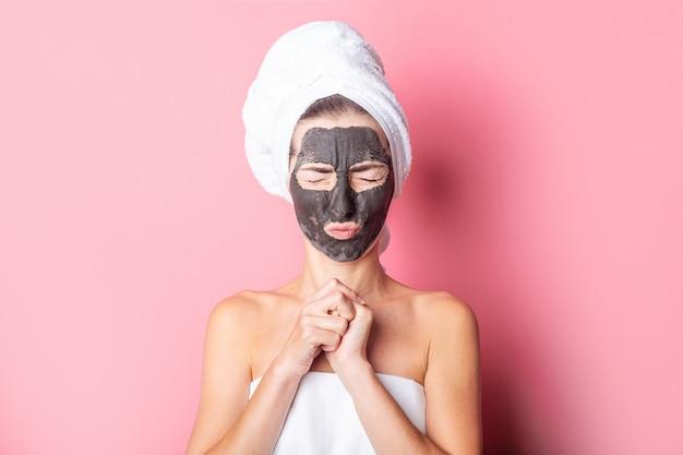 ピンクの背景に黒いフェイスマスクをし、目をしっかりと閉じた若い女性。