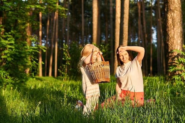 Молодая женщина с дочерью малыша на пикнике в парке смотрят на заходящее солнце