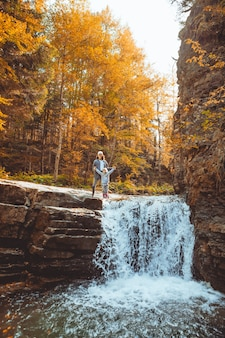 Young woman with toddler girl looking at waterfall at autumn forest hiking concept