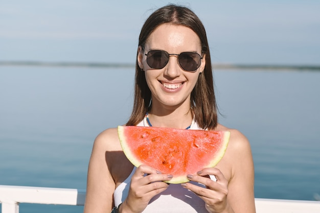 Young woman with toothy smile holding slice of sweet juicy watermelon