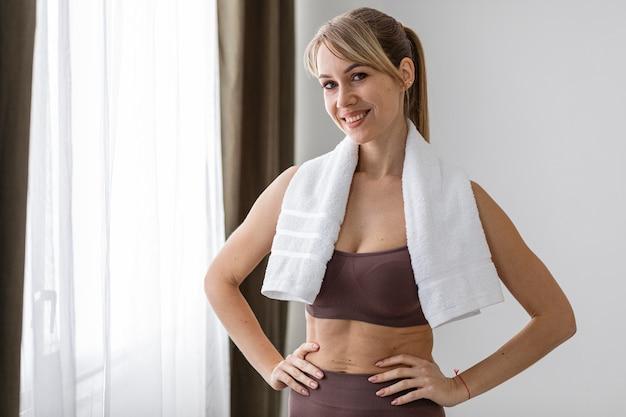 Молодая женщина с полотенцем после тренировки